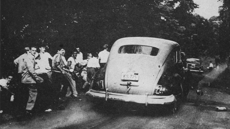 A car of concert-goers runs the gauntlet to the Parkway. This was one of the worst death traps of the various exits. The cars moved slowly and there was no escape from the rocks. Further down the road, at the right, you can see a policeman standing calmly and ovserving the work of the fascist hoodlums.