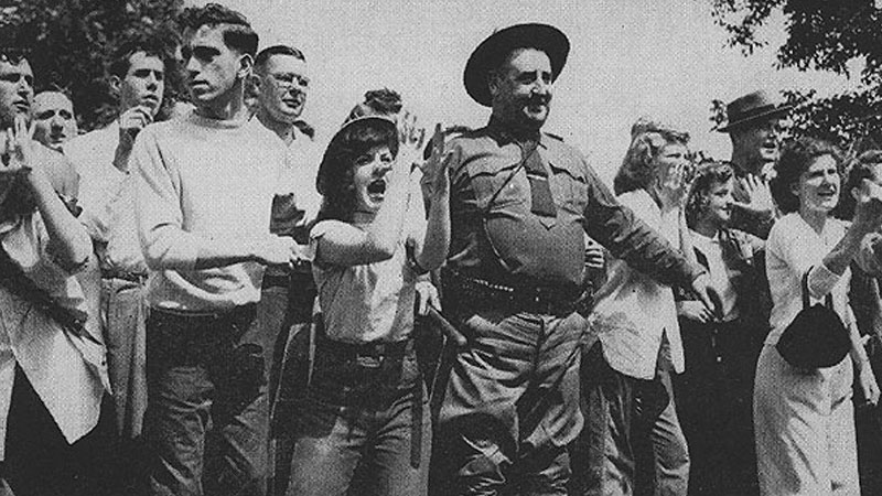This group of young hoodlums, gathered around one of Governor Thomas E. Dewey's state troopers, gives clear pictorial evidence of the dignity and the courage with which the super-patriots defend America.