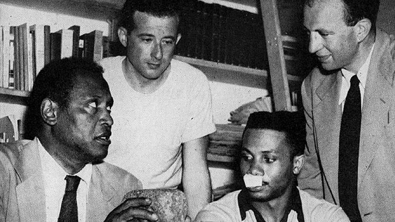 Three of the most important participants in Peekskill: Paul Robeson, to the left, Leon Straus of the International Fur and Leather Workers Union, standing center, and Howard Fast, on the right. The injured man who is seated is Wilson McDowell who was hurt in one of the buses. Paul Robeson holds one of the rocks which crashed into the bus, over a smashed auto window.